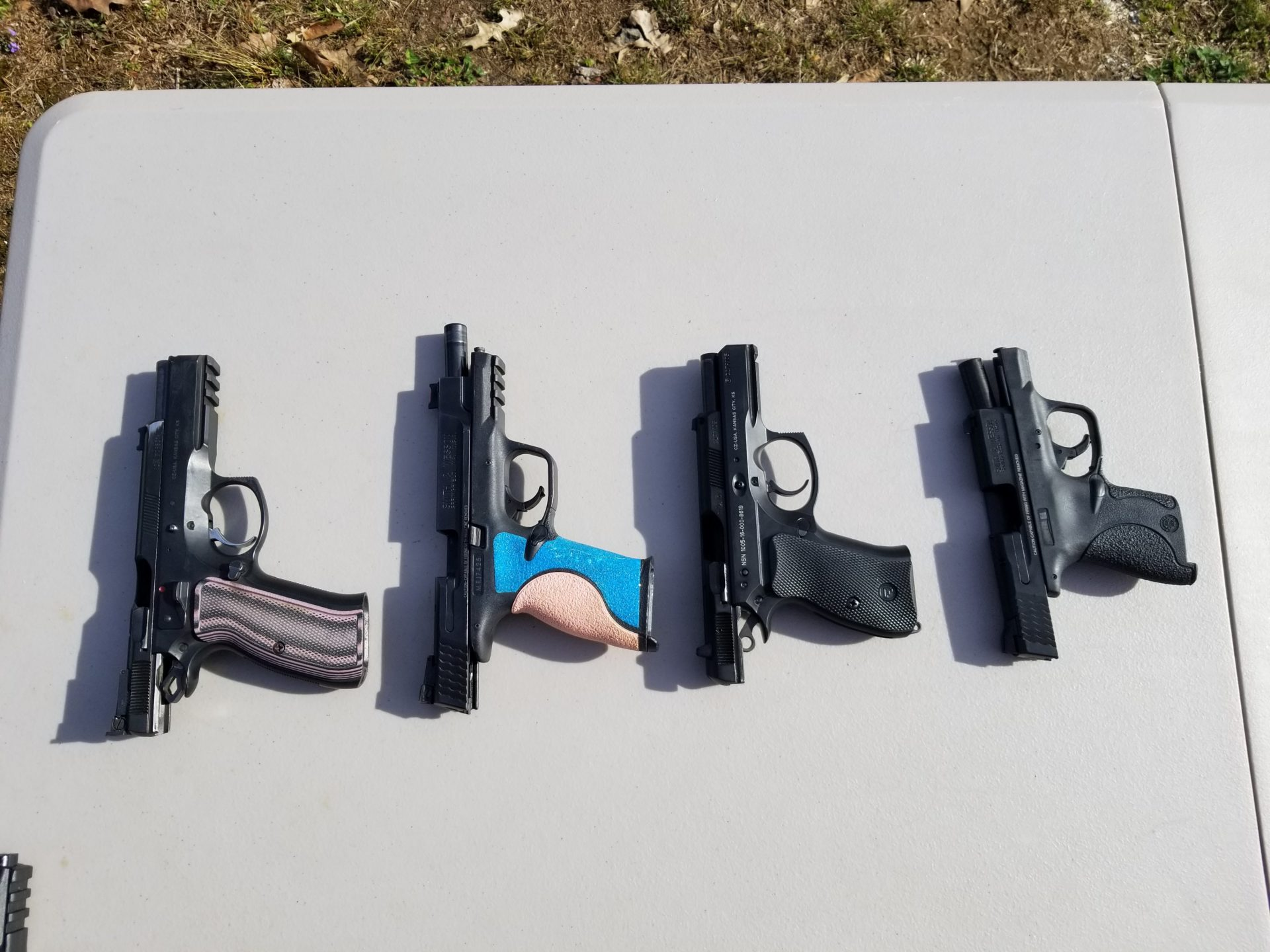 four different guns on a table